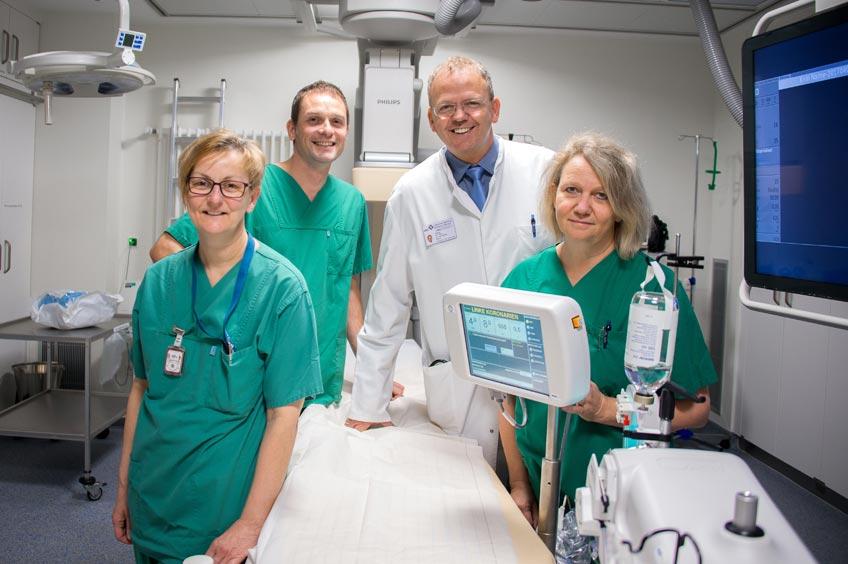 Klinikdirektor PD Dr. Marcus Wiemer (links) und der Leiter des Herzkatheterlabor Dr. Alexander Samol (rechts) freuen sich wenige Stunden nach dem erfolgreichen Eingriff, dass es ihrer Patientin Ursula Bültmann wieder gut geht. Die beiden Herzspezialisten haben Ursula Bültmann vor einer großen Herz-OP verschont.